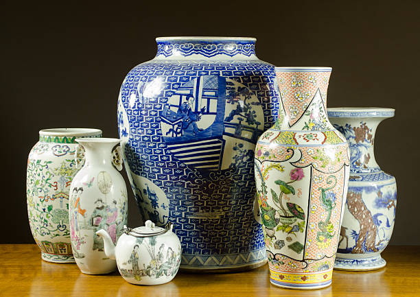 Collection of antique Chinese porcelain vases, urns and teapot.  On a wood table top with black background.