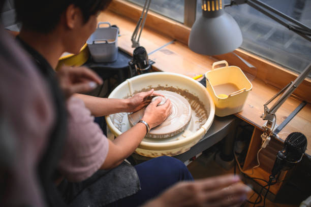 Cropped image of potter molding shape on wheel. Close-up of craftsperson working. He is making clay pot.