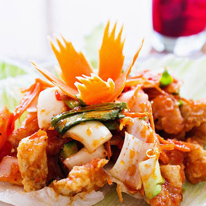 """Thai fish salad: crisply fried fish in batter with chilli, spring onions, tomatoes and sweet and sour sauce, all served in a lettuce cup with the classic Thai carved carrot garnish. A glass of grape juice is in the background."""